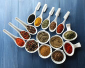 Different kinds of spices in ceramics spoons, close-up, on color wooden background — Stock Photo