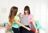 Seçerek ve giysi evde çalışan iki kız — Stok fotoğraf