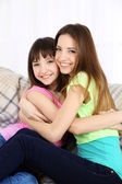 Two girls smiling on home interior background — Stock Photo