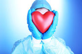 Doctor holding decorative heart on blue background — 图库照片