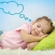 Cute little girl sleeping on colorful pillows and dreaming on blue background — Foto de Stock   #65643869