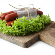 Smoked thin sausages  with lettuce salad leaves on wooden cutting board, isolated on white — Stock Photo #65645171