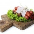 Smoked thin sausages  with lettuce salad leaves on wooden cutting board, isolated on white — Stock Photo #65645181