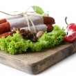 Smoked thin sausages  with lettuce salad leaves on wooden cutting board, isolated on white — Stock Photo #65645189