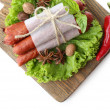 Smoked thin sausages  with lettuce salad leaves on wooden cutting board, isolated on white — Stock Photo #65645195