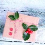 Beautiful Cristmas gift with European Holly (Ilex aquifolium) on wooden background — Stock Photo #65645423