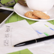 Cup of coffee with pen and business notes on napkin on green bamboo mat background — Stock Photo #65645591