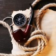 Marine still life pipe, compass, rope and sheet of paper on wooden background — Stock Photo #65647287