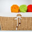 Colorful towels with wicker basket on shelf of rack background — Stock Photo #65648065