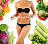 Beautiful young woman measuring her body with tape isolated on white and vegetables around — Stock Photo