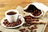 素朴な木製の背景に豆とコーヒーのカップ — ストック写真