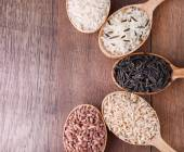 Different kinds of rice in spoons on wooden background — Stock Photo