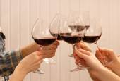 Clinking glasses of red wine in hands on color wooden planks background — Stock Photo
