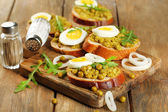 Sandwiches with green peas paste and boiled egg with onion rings and lemon on wooden planks background — Stockfoto