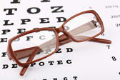 Eye glasses on eyesight test chart background — Stockfoto