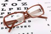 Eye glasses on eyesight test chart background — Stock Photo