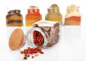 Different kinds of spices in glass bottles isolated on white — Stock Photo