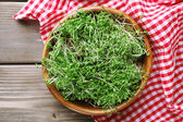 Fresh cress salad in bowl on napkin and wooden planks background — Stock Photo