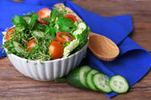 Cress salad with sliced cucumber, cherry tomatoes and parsley in glass bowl on rustic wooden table background — Stock Photo
