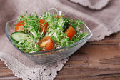 Cress salad with sliced cucumber and cherry tomatoes in glass bowl on rustic wooden table background — Stock Photo