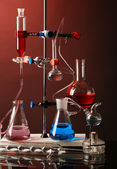 Fixed laboratory glassware on support on dark colorful background — Stock Photo