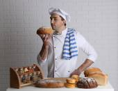 Baker in kitchen at table with freshly loaves of bread on white brick wall background — Stock Photo