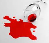 Red wine spilled from glass on white background — Stock Photo