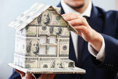 Model of house made of money in male hands on white background — Stock Photo