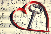 Retro key with heart on music book background — Stock Photo