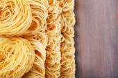 Different dry instant noodles on wooden background — Stock Photo