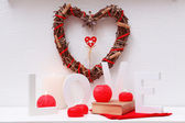 Romantic still life with wicker heart and candle lights on mantelpiece and white wall background — Stock Photo