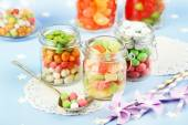 Multicolor candies in glass jars on colorful background — ストック写真