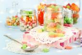 Multicolor candies in glass jars on colorful background — Stock Photo