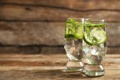 Glasses with fresh organic cucumber water on wooden table — Stockfoto