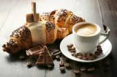 Fresh and tasty croissants with chocolate and cup of coffee on wooden background — Stock Photo