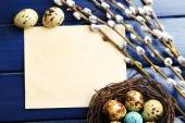 Bird eggs in nest and pussy willow flowers branches on wooden background — Stock Photo