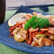 Chinese noodles with vegetables and seafood on plate on bamboo mat background — Stock Photo #65686859