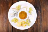 Different sort of cheese with grape and saucer on plate on wooden table background — Fotografia Stock