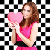 Beautiful young girl with heart in hands on checkered background — Stock Photo