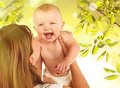 Cute baby boy and his mother on natural background — Stock Photo