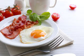 Bacon and eggs on wooden table — Stock Photo