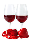 Composition with red wine in glasses, red rose, ribbon and decorative hearts isolated on white — Stock Photo