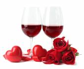 Composition with red wine in glasses, red roses, ribbon and decorative hearts isolated on white — Foto de Stock