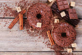 Delicious donuts with icing and chocolate crumb on wooden background — Stock Photo