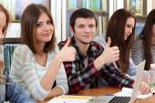 Group of students sitting at table in library — Stock Photo