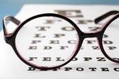 Glasses on eye chart close-up — Stockfoto