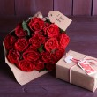 Bouquet of red roses wrapped in paper and present box on wooden background — Stock Photo #66158882