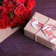 Bouquet of red roses wrapped in paper and present box on wooden background — Stock Photo #66158884
