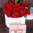 Bouquet of red roses in textile box with present on wooden background — Stock Photo #66159092