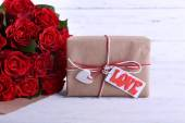 Bouquet of red roses wrapped in paper and present box on wooden background — Stock Photo